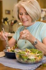 Older woman preparing a healthy salad