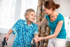 Caregiver and elderly woman with walker